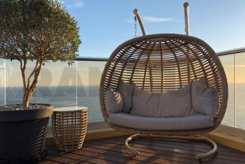 лучи вечернего заката проникают сквозь плетение подвесного кресла ФРЕСКО на веранде пентхайса в Сочи