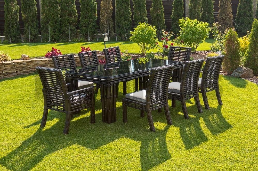 Обеденный стол со стульями из искусственного ротанга цвета бронза на открытой площадке загородного дома фото